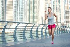De atleet stelt en maakt de training in werking Atletische vrouw in sportkleding Stock Afbeelding