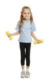 De atleet van het zes éénjarigenmeisje belast met oefening met domoren Stock Fotografie