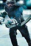 De atleet van de ijshockeyspeler in de helm en handschoenen op stadion met stok Actieschot Het concept van de sport stock foto