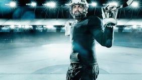 De atleet van de ijshockeyspeler in de helm en handschoenen op stadion met stok Actieschot Het concept van de sport stock fotografie