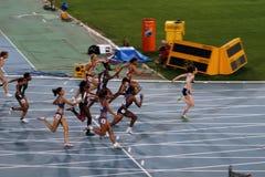 De atleten concurreren in het 4x100 relaisras royalty-vrije stock fotografie