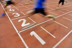 De atleten kruisen de afwerkingslijn Stock Fotografie