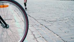 De atleten lopen langs een bedekte weg voorbij een fietser, een mening van de doornemende mensen het wiel van een fiets, stad stock footage