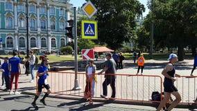 De atleten lopen voorbij de bouw van het de Winterpaleis in St. Petersburg tijdens de marathon Franse ventilatorssteun Frankrijk stock footage