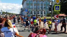 De atleten op de achtergrond van de bouw van het de Winterpaleis in St. Petersburg beëindigen de marathon van St. Petersburg Over stock videobeelden