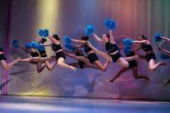 De atleten presteren op stadium, presteren jonge cheerleaders bij het cheerleading kampioenschap, houden de meisjes in een sprong stock afbeeldingen