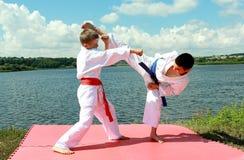 De atletenkinderen voeren in paren gerangschikte oefeningenkarate uit Royalty-vrije Stock Afbeeldingen