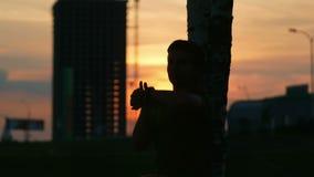 De atletenmens die bij zonsondergang rusten en controleert de impuls een slim horloge Stadslandschap met auto's en bouwwerf stock videobeelden