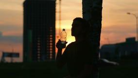 De atletenmens die bij zonsondergang rusten en drinkt water van een fles Zon in het water prachtig wordt weerspiegeld dat Het lan stock video