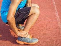 De atletenmens heeft enkelverwonding, verstuikt been tijdens het lopen traini stock foto's