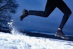 De atletenmens loopt tijdens de winter opleiding buiten in koud sneeuwweer stock foto