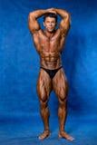 De atletieksportbodybuilder toont houding aan Royalty-vrije Stock Foto
