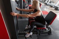 De atletische jonge vrouw in modieuze zwarte sportkleding in tennisschoenen werkt aan een simulator in de gymnastiek Het meisje d stock fotografie