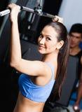 De atletische jonge vrouw werkt in gymnastiek uit Stock Foto's