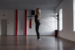 De atletische jonge vrouw in zwarte sportkleding springt op een touwtjespringen en brandt calorieën in een geschiktheidsstudio Me stock foto's