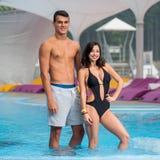De atletische kerel en het meisje met een perfect cijfer dichtbij het zwembad op luxeberg nemen met vage achtergrond zijn toevluc Stock Foto