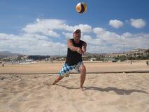 De atletische mens baggert beachvolleyball uit Stock Foto