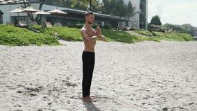 De atletische mens die yoga op strand met zijn handen samen en ogen doen sloot, langzaam motie steadicam schot stock videobeelden