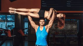 De atletische mens heft geschiktheidsmeisje als gewicht over himsself in gymnastiek op Stock Foto's