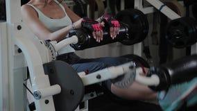 De atletische mooie vrouw presteert op de uitbreiding van het simulatorbeen stock footage