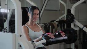 De atletische mooie vrouw presteert op de uitbreiding van het simulatorbeen stock video