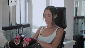 De atletische mooie vrouw presteert op de uitbreiding van het simulatorbeen stock videobeelden