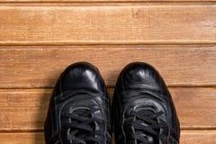 De atletische schoenen van geschiktheidsconcepten op houten achtergrond Oude betrouwbare zwarte leertennisschoenen Stock Afbeelding