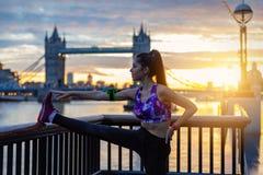 De atletische stadsvrouw doet haar rek voor Torenbrug in Londen royalty-vrije stock fotografie