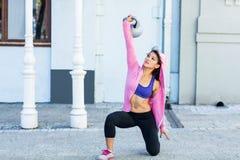 De atletische vrouw die Turks uitoefenen staat met kettlebell op Royalty-vrije Stock Afbeelding