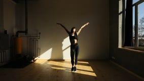 De atletische vrouw doet pilates Zij warmt door handen op te heffen en bekken in de studio op te bewegen stock video