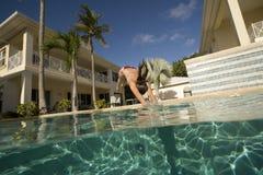 De atletische vrouw duikt in zwembad stock afbeelding
