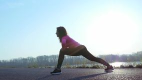 De atletische vrouw gaat binnen voor sporten op de rivierbank bij zonsopgang Langzame Motie stock video