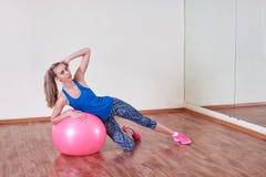 De atletische vrouw maakt oefeningen op een geschiktheidsbal, binnen gymnastiek stock foto