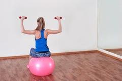De atletische vrouw maakt oefeningen op een geschiktheidsbal, binnen gymnastiek stock afbeeldingen