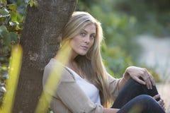 De Australische Schoonheid met Lang Blond Haar zit door een boom Royalty-vrije Stock Fotografie