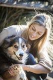 De Australische Schoonheid met Lang Blond Haar zit met haar colliehond Stock Foto's