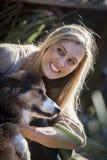 De Australische Schoonheid met Lang Blond Haar zit met haar colliehond Stock Foto
