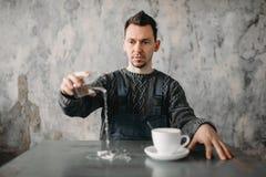 De autistische mens giet water van het glas op lijst royalty-vrije stock fotografie