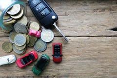 De auto bedrijfskosten als onderhoud of verzekering met stuk speelgoed auto's, de geldbesparingen en de auto sluiten op houten ac Stock Foto's