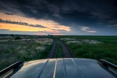 De auto berijdt op een landweg in het gebied, de mooie zonsondergang met wild gras, het zonlicht en de donkere wolken Stock Afbeelding