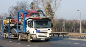 De auto-carriervrachtwagen levert nieuwe autopartij aan handelaar stock foto's