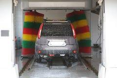 De auto in een automatische autowasserette. Stock Afbeeldingen
