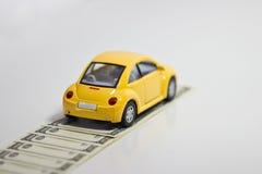 De auto en het geld van het stuk speelgoed Stock Foto