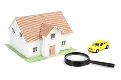De auto en het huis van het stuk speelgoed met meer magnifier Royalty-vrije Stock Foto's