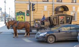 De auto en paardbemanning bevindt zich op het verkeerslicht in Petersburg stock afbeelding