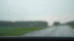 De auto gaat op de weg Het is regenende harde buitenkant, werken de ruitewissers Regendruppels op Glas stock video