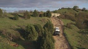 De auto gaat zorgvuldig onderaan gebroken berglandweg De eenzame bouw op heuvel stock videobeelden