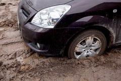 de auto is geplakt op een slechte weg in de modder Royalty-vrije Stock Afbeeldingen