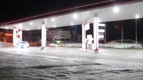 De auto komt aan benzinepost en tankt bij nacht in de winter bij stock video