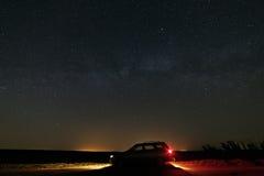 De auto met de koplampen schakelde de achtergrondmelkweg in royalty-vrije stock foto's